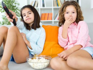Kids watching Television with Popcorn and Remote Control