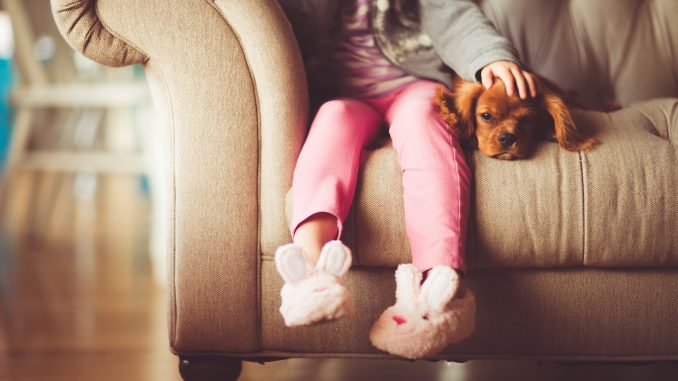 Little Girl on Couch with Puppy